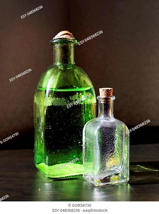 Still life with two small color vintage glass bottles on the table against a low key background. Shallow depth, selective focus