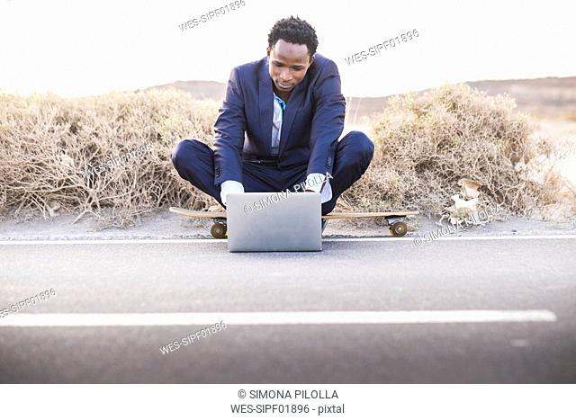 Spain, Tenerife, young businessman sitting on skateboard and using laptop