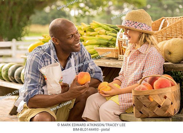 Vendor talking to girl at farmers market