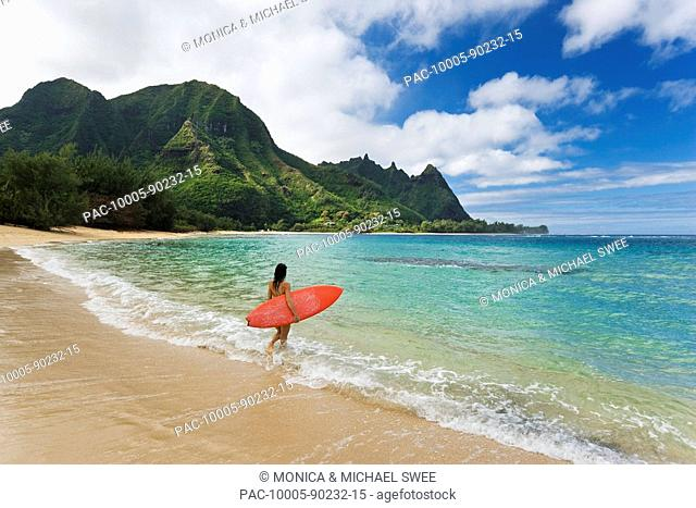 Hawaii, Kauai, Haena Beach Tunnels Beach, Woman entering ocean with surfboard