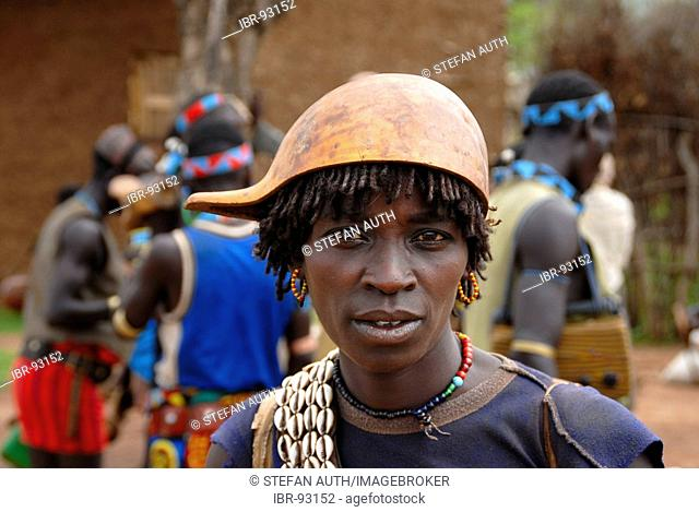 Portrait woman wearing a chain of kauri mussels and a kalabasse on her head on the market of Keyafer Ethiopia