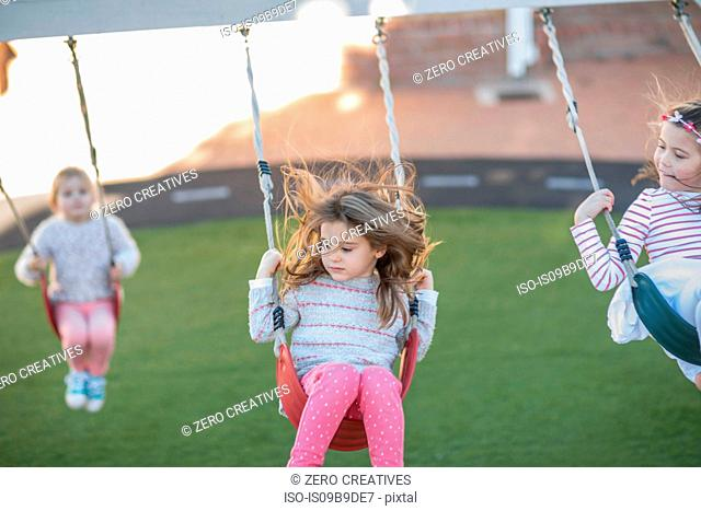 Girls at preschool, swinging on playground swings in garden