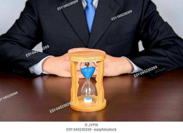 Businessman with hands behind back of an hourglass