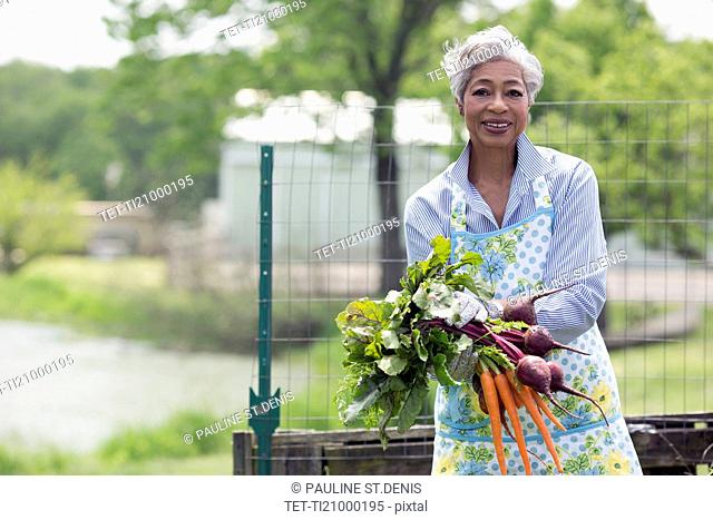 Portrait of senior woman holding carrots and beetroot