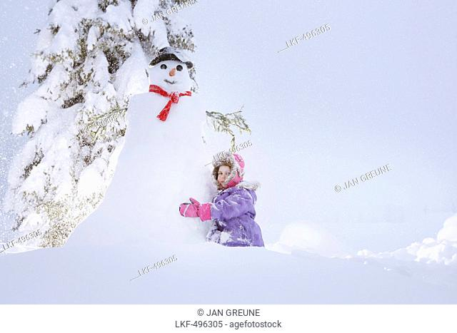 Girl crouching beside a snowman, Passo Monte Croce di Comelico, South Tyrol, Italy
