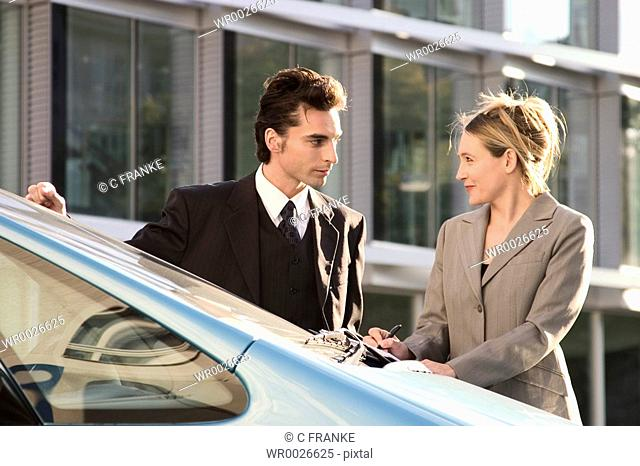 Businessman and businesswoman looking at each other near car