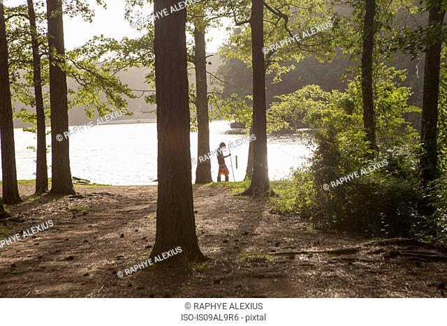 Teenage boy fishing at forest lake, Arkansas, USA