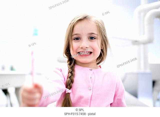 MODEL RELEASED. Close-up of girl holding toothbrush
