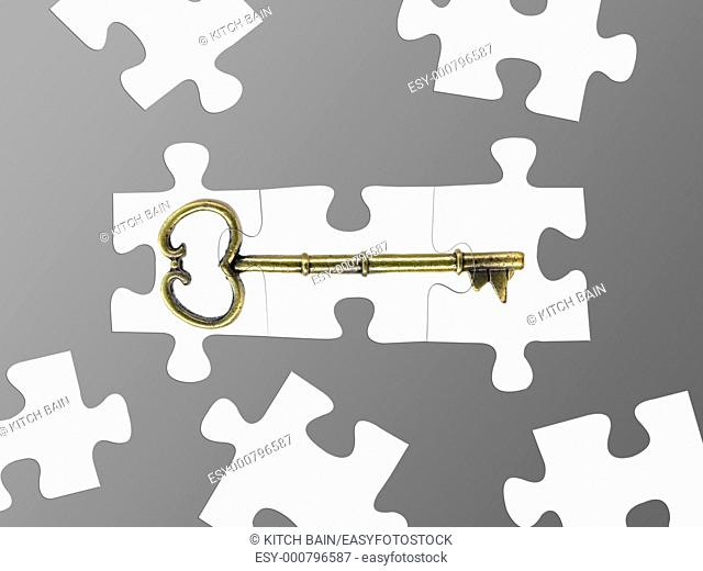 Jigsaw puzzle pieces of a key isolated against a grey background