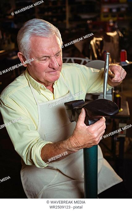 Shoemaker making a shoe with hammer