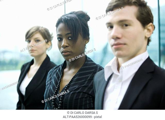 Three business associates standing side by side looking at camera