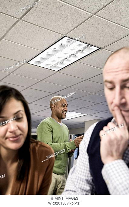 Mixed race team of three people working on a project in an office cubicle area