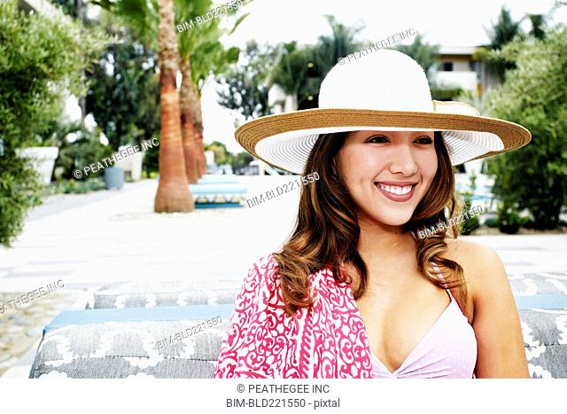 Hispanic woman wearing sun hat outdoors