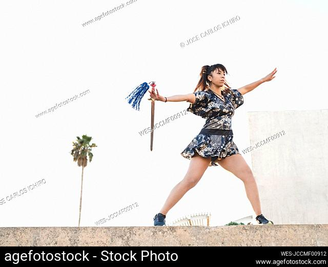 Young female athlete with sword practicing martial arts on retaining wall against clear sky