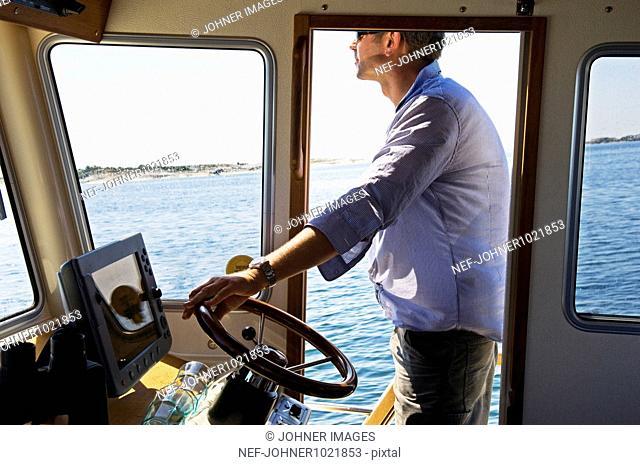 Sweden, Stockholm, man steering small nautical vessel