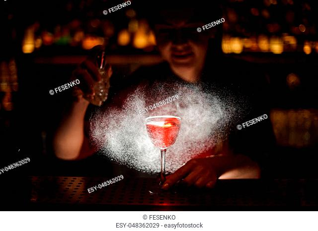 Barman girl decorating a glass of alcoholic cocktail with spray on the dark blurred background