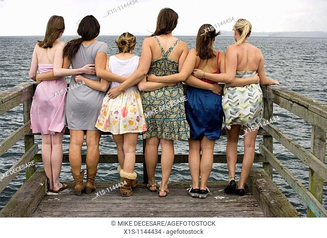 At the end of a pier, six young women with their backs to the camera are connected by arms as they look out into the water