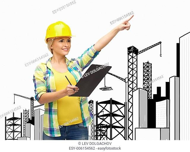 repair, construction and maintenance concept - smiling woman in helmet with clipboard pointing finger