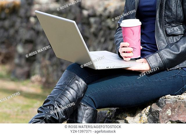 Female student with a laptop and coffee