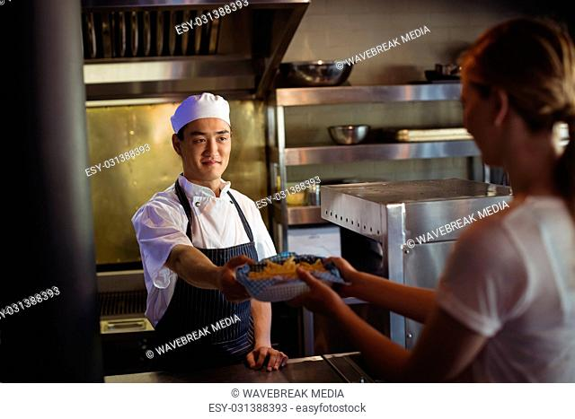 Chef passing tray with french fries to waitress
