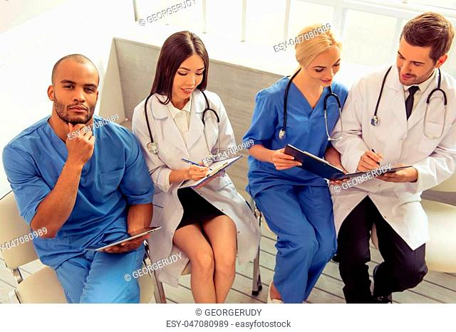 Group of medical doctors of different nationalities and genders with folders and tablet is examining documents and smiling, sitting in office