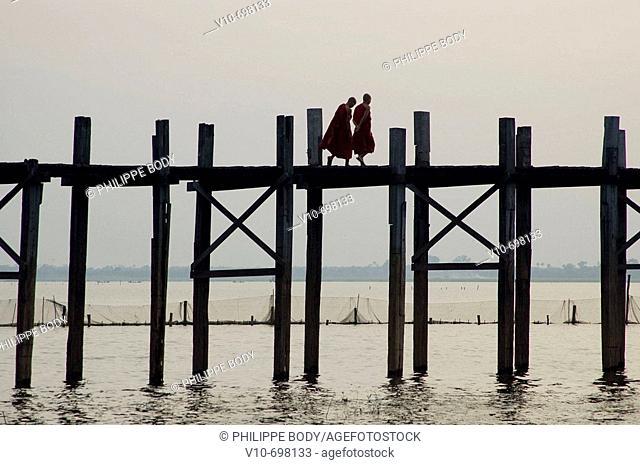 Buddhist monks on the U Bein bridge in teak wood in the old royal city of Amarapura near Mandalay, Myanmar