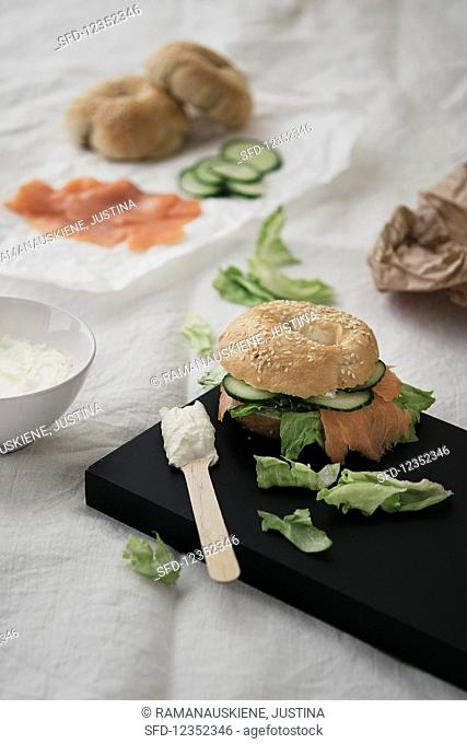 A salmon bagel with cucumber, lettuce and cream cheese