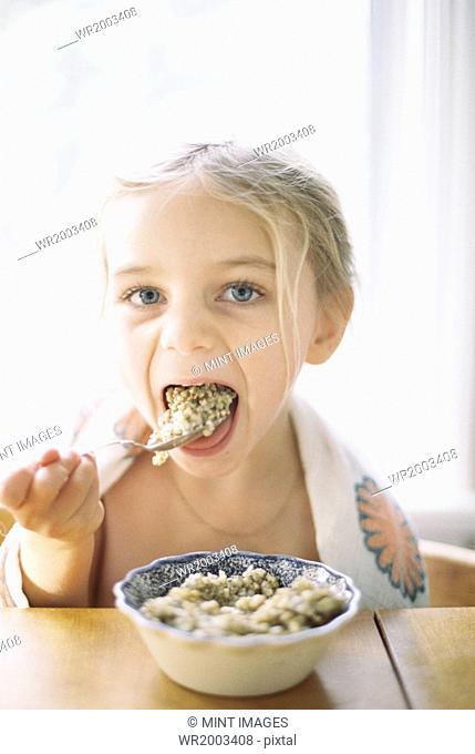 Young girl sitting at a table, eating breakfast from a bowl