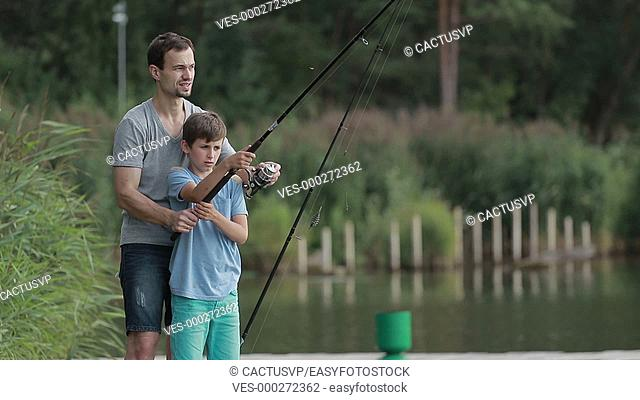 Teenage boy learning to fish with father's help