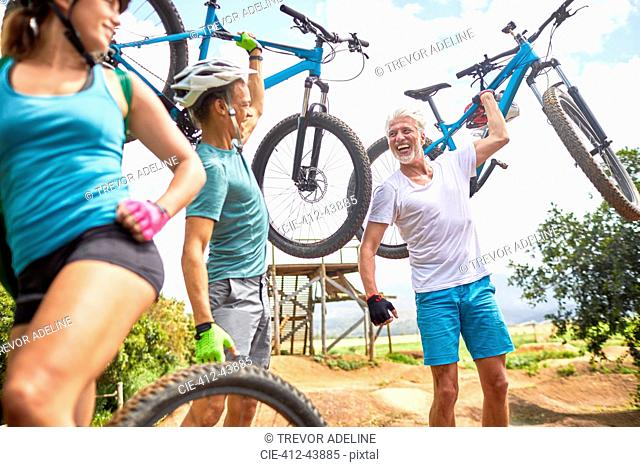 Carefree friends carrying mountain bikes