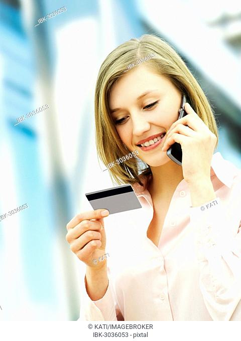 Businesswoman using a mobile phone and holding a card