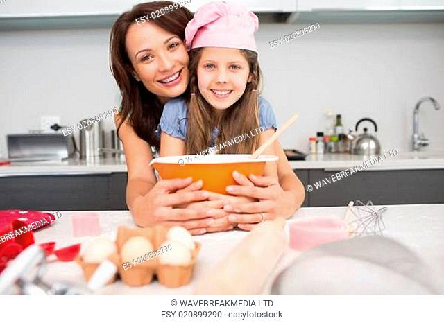 Portrait of a girl and mother preparing cookies in kitchen