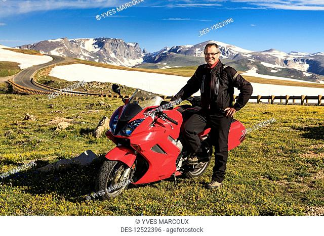 View from the Beartooth Highway of the Beartooth Mountains and a man posing with a motorcycle parked on the roadside; Cody, Wyoming, United States of America