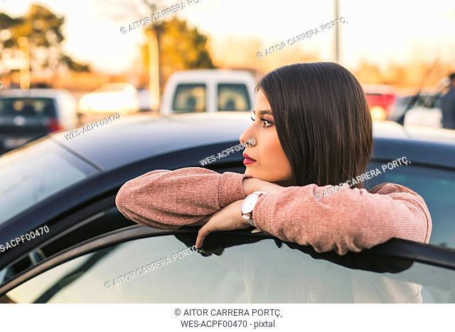 Teenage girl leaning on car door looking at distance