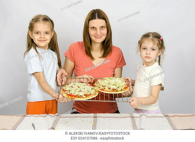 Mom and two small daughters show the two had not yet made baked pizza on a baking sheet