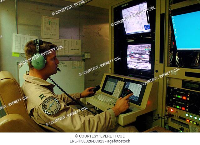 An Air Force officer maneuvers an unmanned Predator reconnaissance airplane over Iraq by remote control at Balad Air Base Iraq. July 2 2004