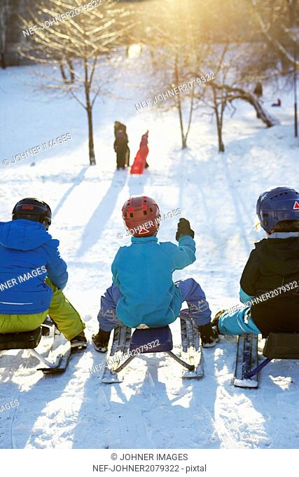 Children on snow scooters at winter