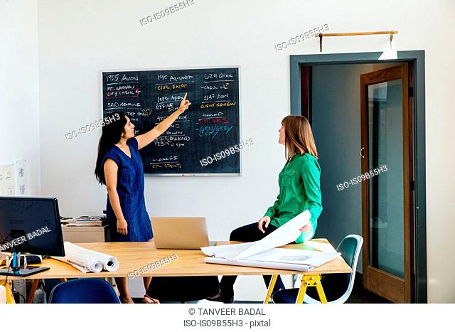 Woman in office giving presentation to colleague