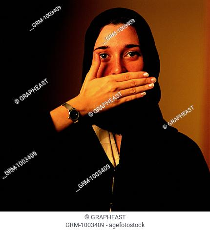 Arab woman covering her mouth with hand