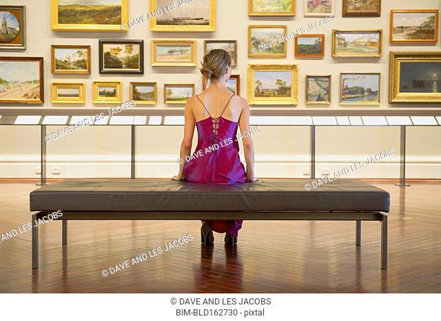 Caucasian woman in evening gown admiring art in museum