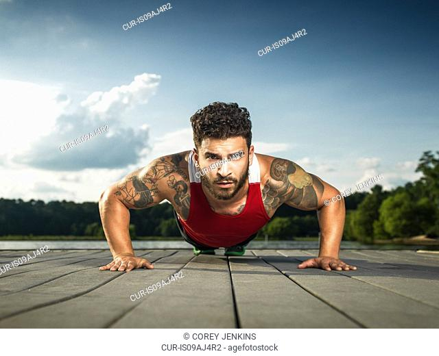 Surface level portrait of young man doing push ups on lake pier