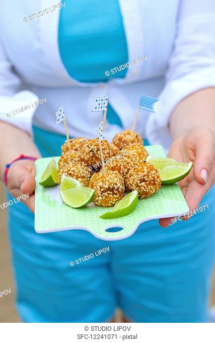 A woman serving fish balls with celery, onion and sesame on a board