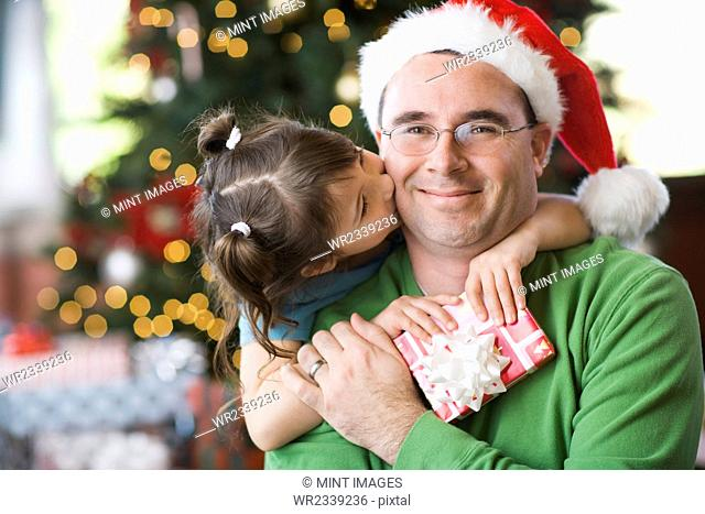 A man and a girl, father and daughter, hugging and exchanging presents by a Christmas tree