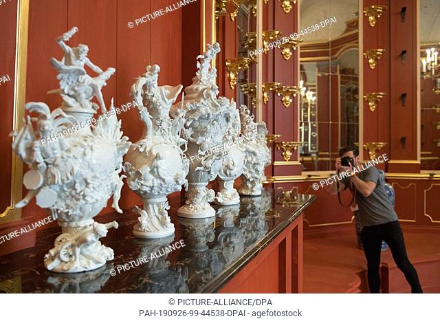 26 September 2019, Saxony, Dresden: A man photographs porcelain element vases in the porcelain cabinet of the tower room as part of a press tour of the...