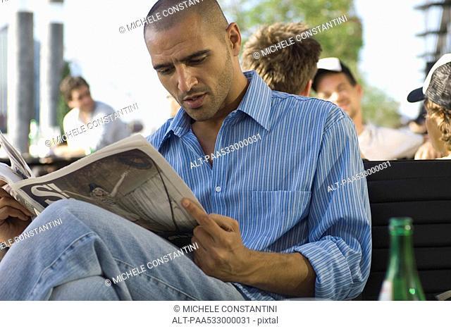 Man reading newspaper outdoors