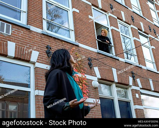 Young woman talking through window with female friend standing outside