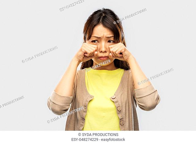 sad asian woman crying over grey background