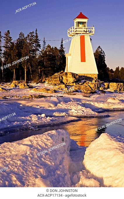 South Bay Lighthouse reflected in ice build-up along Georgian Bay shoreline, South Bay, Manitoulin Island, Ontario, Canada