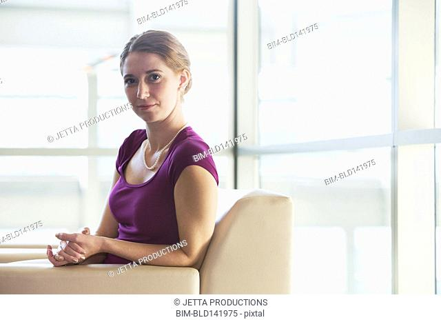 Caucasian businesswoman sitting in office lobby