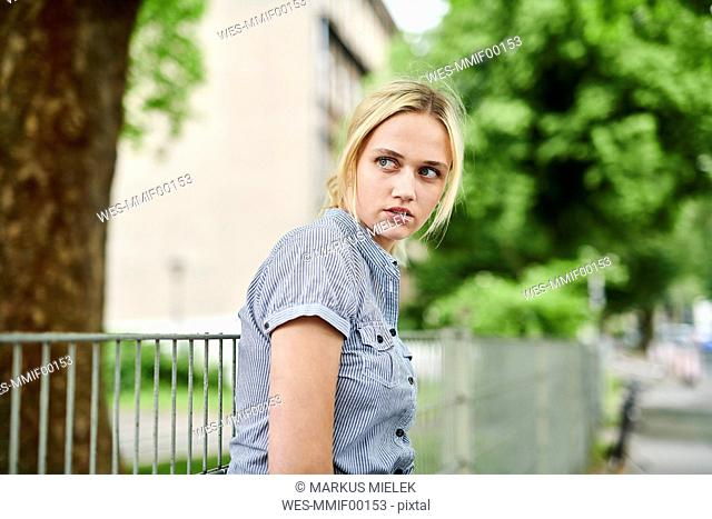 Serious blond young woman at a fence